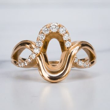 Rose Gold Saddle Ring with diamonds on a White Marble Surface
